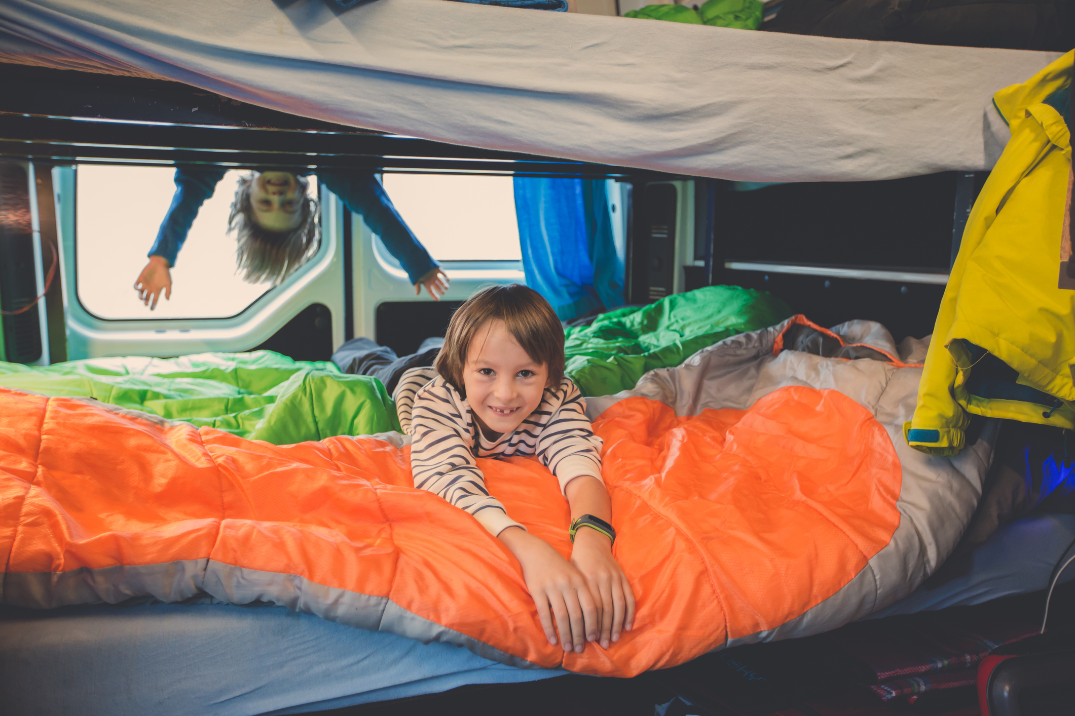 Children, having fun in camper van while heavy raining outdoors, playing and making mischiefs together